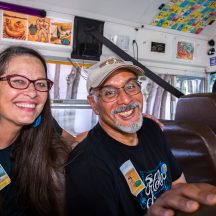 Book and Wheel artists, Kate Connell and Oscar Melara are pictured on the Mexican Bus during the 5.5 Mile Road House Tour. Both are smiling. Kate has long hair and glasses.and Oscar has a ball cap on.