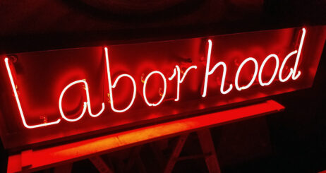 "The image is of a neon sign that reads ""Laborhood"" in red against a dark background."