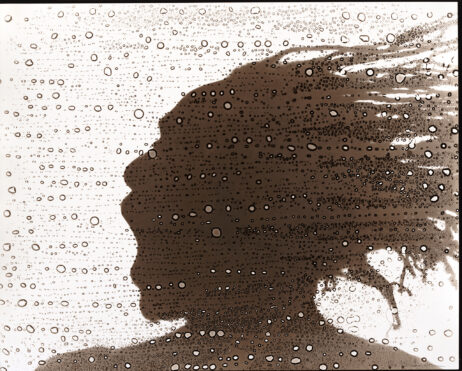 Silhouette of a man's head with dreads blowing behind him face a spray of water drops