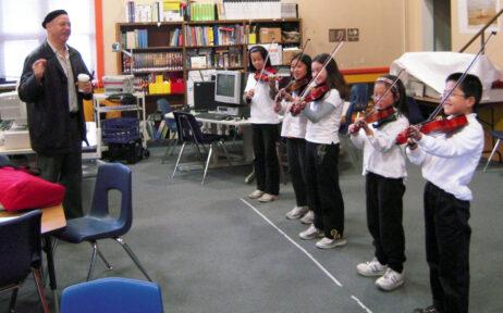 Dr. John Calloway teaching students violin at E. R. Taylor elementary school